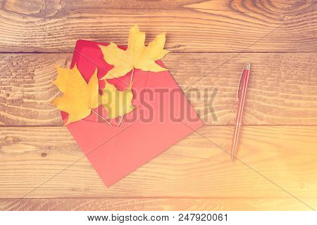 Red Envelope With Autumn Leaves. Autumn Letter. Maple Leaves In Red Envelope, Red Pen On Wooden Back