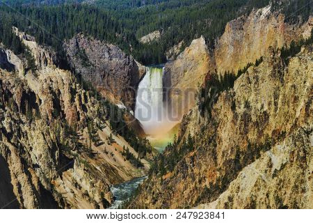 The mist in the Lower Falls in Yellowstone National Park creates a rainbow when the light is just right.  This landmark is located in Wyoming.