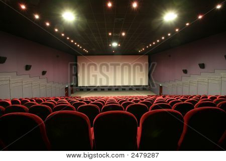 Empty Cinema Auditorium With Red Chairs And Screen