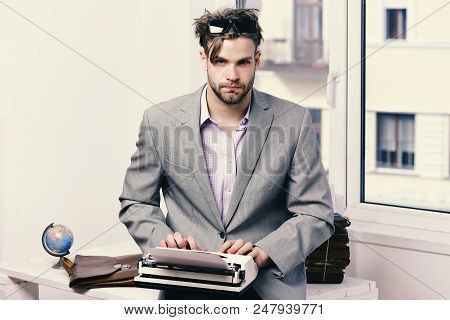 Man With Serious Face Types Story Or Business Report. Young Author Or Editor Writes Story On Old Typ
