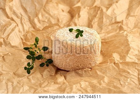 Crottin Cheese With Thyme Leaves On Brown Package Paper.