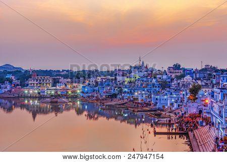 Pushkar Holy Lake At Sunset. Hindu Pilgrims Bathing In Sacred Lake Pushkar (sarovar) On Ghats. Count