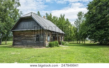 Rural Architecture. An Old Rural House Made Of Logs, Grass Grows Around The House.