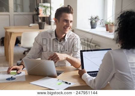 Smiling Millennial Colleagues Talking While Working At Laptops, Employees Discussing Business Projec