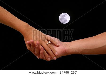 Engagement. A couple holds hand with the full moon sky background. Romantic Engagement with wedding right and full moon.