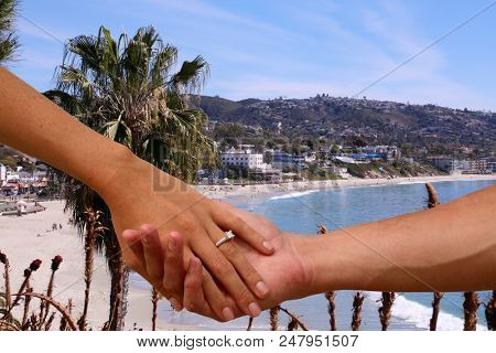 Engagement Couple holding hands with a beach background. A couple hold hands with a wedding ring and Laguna Beach California Background.