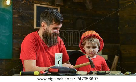 Fatherhood Concept. Boy, Child Busy In Protective Helmet Learning To Use Hammer With Dad. Father, Pa
