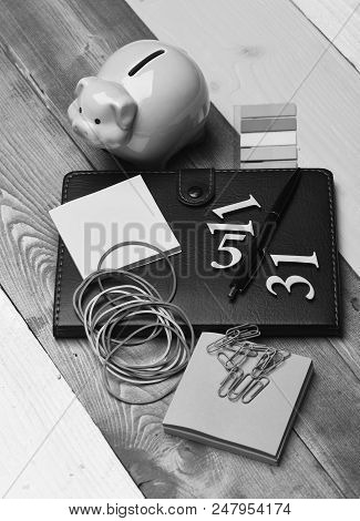 Home Finance Composition. Piggy Bank And Stationery On Colorful Wooden Background. Moneybox With Pig