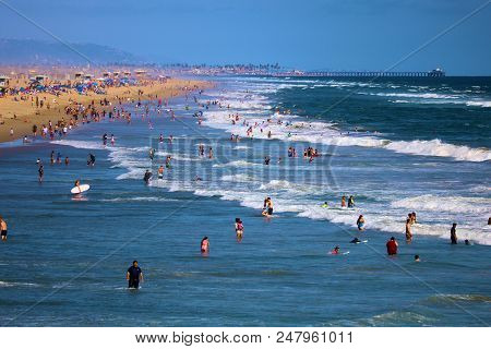 July 2, 2018 In Huntington Beach, Ca:  People Swimming In The Ocean And Sunbathing On The Sandy Beac