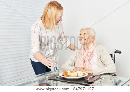 Nursing lady serves old woman a meal in a nursing home or at home