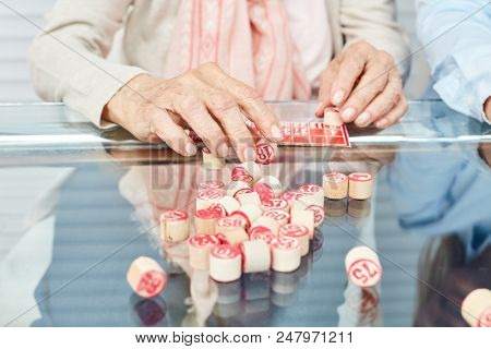 Hands of seniors playing bingo as a memory training in the retirement home