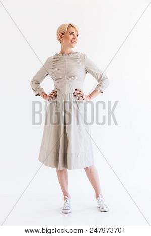 Full length portrait of charming blond adult woman 40s wearing dress looking aside at copyspace with candid smile and hands on waist isolated over white background in studio