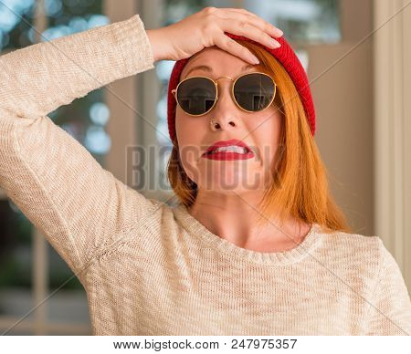 Stylish redhead woman wearing wool cap and sunglasses stressed with hand on head, shocked with shame and surprise face, angry and frustrated. Fear and upset for mistake.
