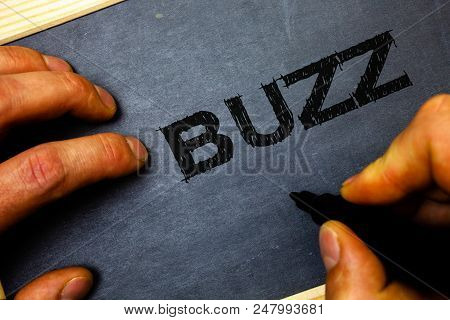 Word writing text Buzz. Business concept for Hum Murmur Drone Fizz Ring Sibilation Whir Alarm Beep Chime Man hold holding black marker markers notebook wood wooden background poster