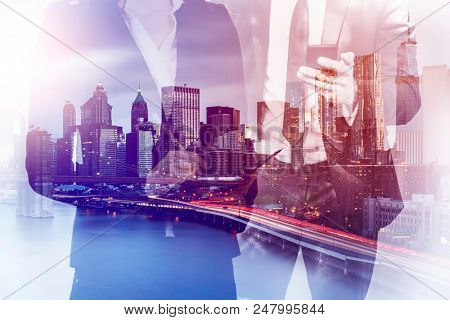 double exposure image of a business man and woman using mobile devices during sunset overlay with cityscape image. modern life and business concept