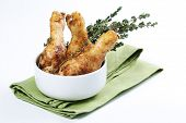 Roasted chicken legs with thyme in a bowl poster
