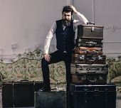 Move out and relocation concept. Man with beard and mustache packed luggage, white interior background. Macho elegant on tired face, exhausted at end of packing, leans on pile of vintage suitcases. poster