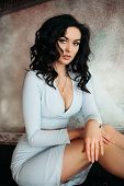 Portrait of hot brunette woman wearing in blue low neckline dress posing at camera. Sexy gorgeous girl with perfect make up after beauty salon and volumed hairstyle. Concept of beauty. poster