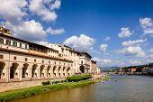 Florence cityscape with Arno River embankment, Vasari Corridor (Corridoio Vasariano) elevated passageway and Uffizi Gallery art museum and Ponte alle Grazie bridge in background, Tuscany, Italy poster
