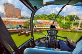 Helicopter cockpit interior flying on Clarke Quay and Riverside area in Singapore. Scenic flight above waterfront skyline with cruise boat on Singapore River in a sunny day. poster