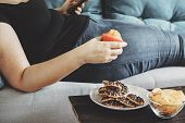 Sugar addiction, unhealthy lifestyle, weight gain, dietary, healthcare and medical concept. Cropped portrait of overweight woman laying on sofa eating sugary foods poster