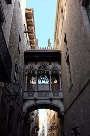 Back Alley In Barcelona (catalonia, Spain) With Ancient Sheltered Bridge Between Two Buildings. Orna