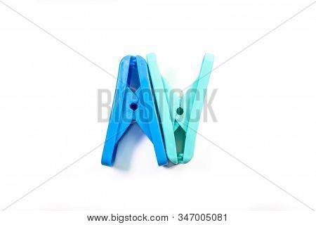 The Close Up Of Light Green Clothes Peg And Blue Clothes Peg On White Background.
