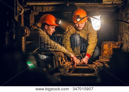 Two Miners In The Mine. A Tired Miners In A Coal Mine Looks At The Light. Work In A Coal Mine. Portr