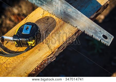 Saw With A Construction Tape Measure On Wooden Board. Wooden Plank. Beams. Air-drying Timber Stack.