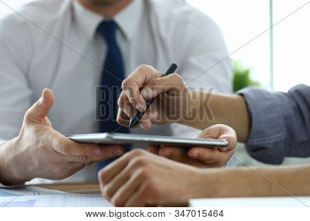 Close-up Of Workers Discussing New Start-up. Customer Signing Electronic Document In Office. Man Poi