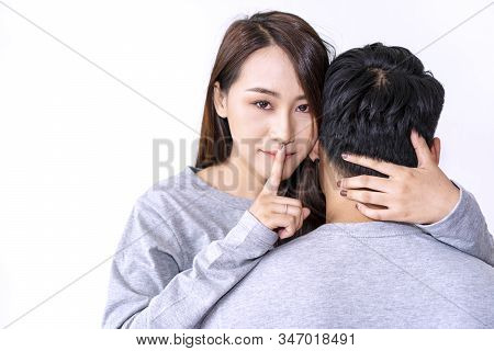 Young Women Embracing Her Husband While Showing Silence Sign With Forefinger Touching Secret Mysteri