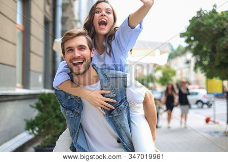 Handsome Young Man Carrying Young Attractive Woman On Shoulders While Spending Time Together Outdoor