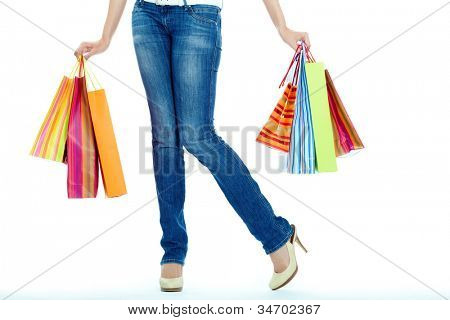 Image of shopaholic legs and shopping bags in hands