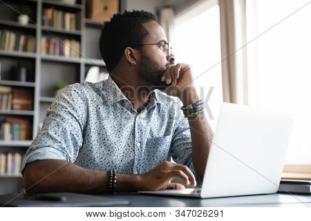 Thoughtful Serious African Man Sit With Laptop Thinking Of Project