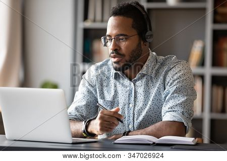 Focused African Businessman Wear Headphones Study Online Watching Webinar