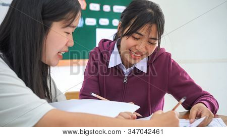 Two Asian Students Laughing Doing Project Homework Together With Successful In Classmate Helping Eac