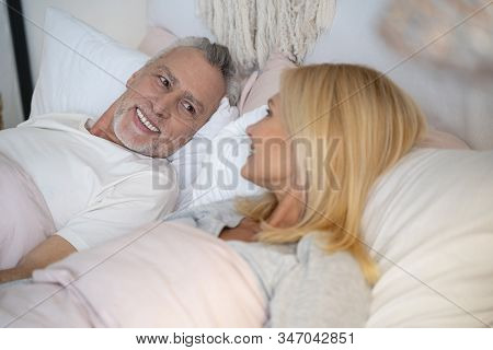 Mirthful Man And Woman In Bed Stock Photo