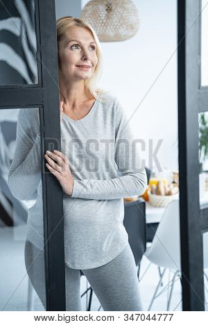 Mirthful Lady By The Glass Door Stock Photo