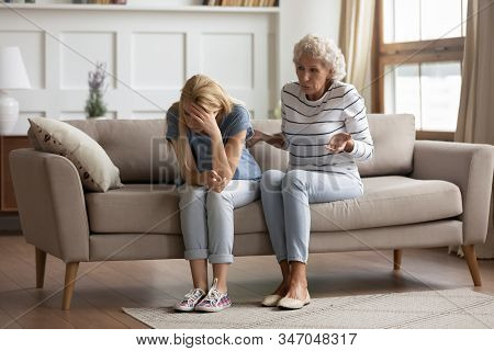 Stressed Millennial Blonde Woman Ignoring Angry Senior Old Mother.