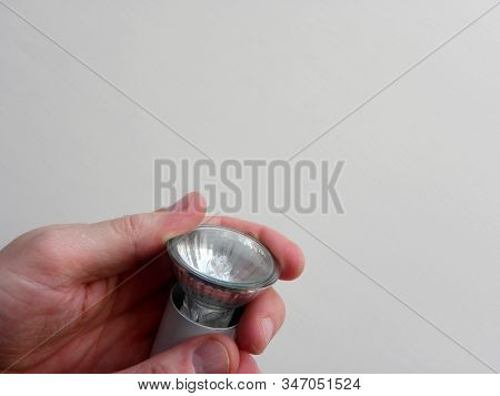 Replace The Led Bulb With Your Own Hands. A Man Unscrews A Burned Out Light Bulb.