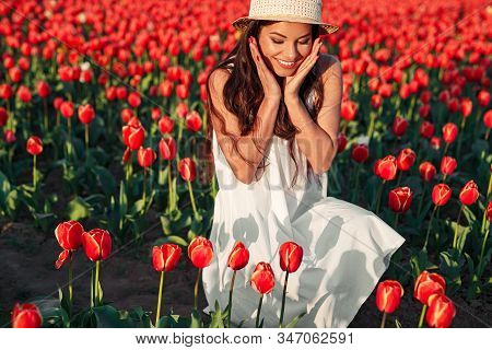 Cheerful Young Female In White Sundress And Hat Enjoying Springtime On Tulip Farm And Admiring Beaut