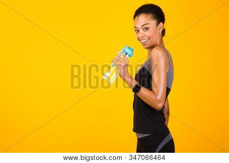 Happy Afro Girl In Fitwear Holding Bottle Of Water Posing Over Yellow Studio Background. Workout And