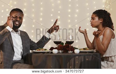 Annoyed Afro Woman Looking At Her Man Talking By Phone While Having Date In Restaurant, Conflicts In