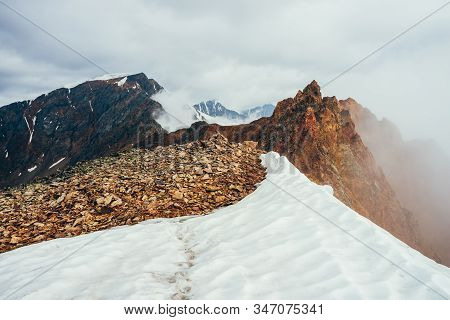 Pointy Rocky Pinnacle On Mountain With Snow Among Thick Low Clouds. Atmospheric Alpine Landscape. Fo