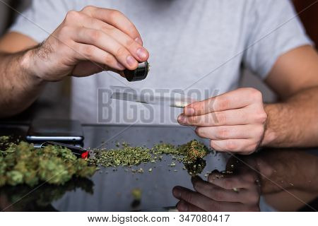 Drug Use. Man Preparing And Rolling Marijuana Cannabis Joint. Close Up Of Addict Lighting Up Marijua