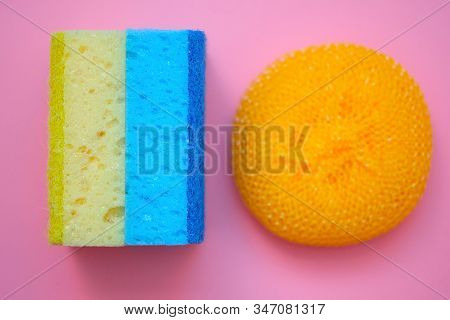 Two Washcloths And A Plastic Brush For Washing Dishes. Bilateral Foam Rubber Washcloths On A Pink Ba