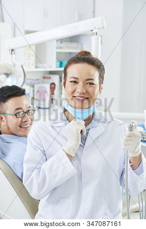 Vertical Medium Portrait Of Beautiful Woman Wearing White Coat Working In Dental Clinic With Her Pat