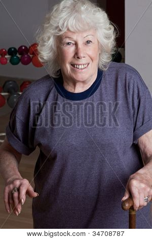 Portrait of senior woman with walking stick.
