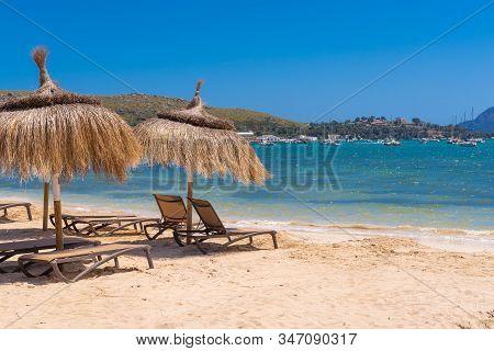 Straw Umbrellas With Sunbeds On The Sandy Beach In Beautiful Port De Pollenca. Mallorca. Spain