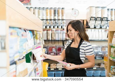 Beautiful Saleswoman Arranging Food Products On Shelf In Grocery Store